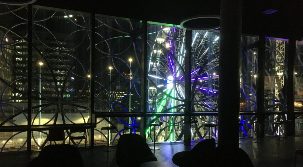 Night time view of illuminated ferris wheel seen from within the Library of Birmingham